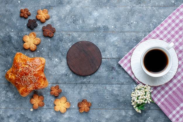 Bovenaanzicht van een kopje koffie samen met gebak, cake en heerlijke koekjes op grijs bureau, zoete bak gebak suiker cake Gratis Foto