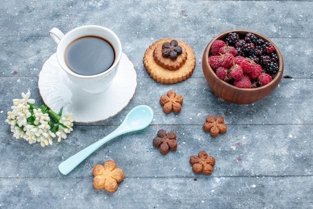 Bovenaanzicht van een kopje koffie samen met kleine koekjes en verse bessen op grijze houten, zoete suiker bak gebak cookie koekje Gratis Foto