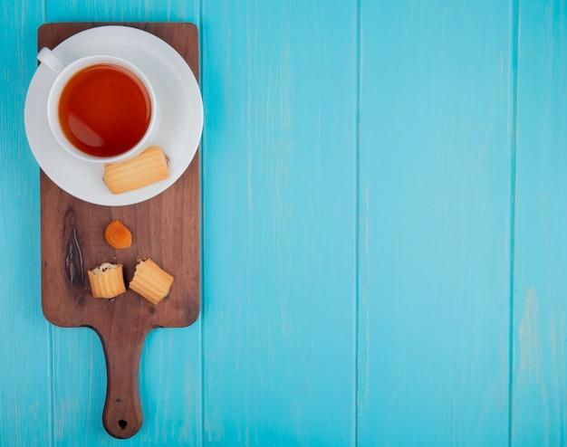 Bovenaanzicht van een kopje thee met koekjes en gedroogde abrikoos op houten snijplank op blauw met kopie ruimte Gratis Foto