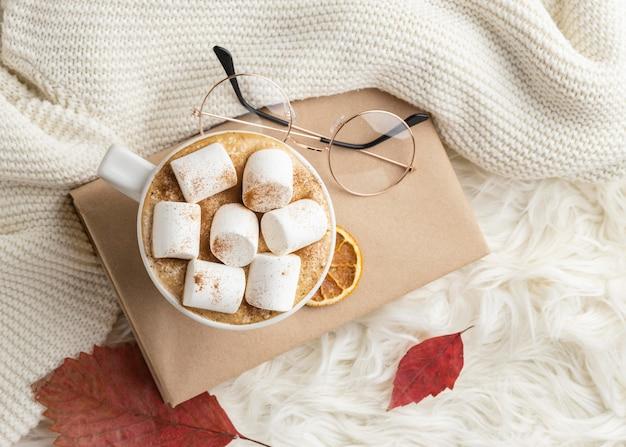 Bovenaanzicht van een kopje warme chocolademelk met marshmallows op boek met glazen Gratis Foto