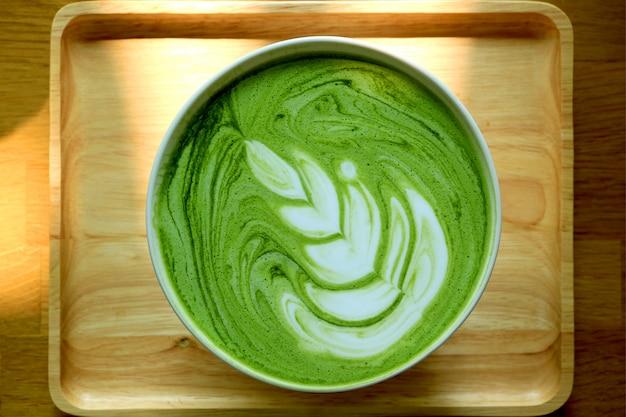 Bovenaanzicht van een kopje warme matcha groene thee latte op natuurlijke houten dienblad Premium Foto