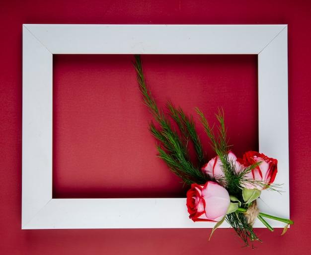 Bovenaanzicht van een leeg afbeeldingsframe met kleine boeket rode rozen met venkel op rode achtergrond met kopie ruimte Gratis Foto