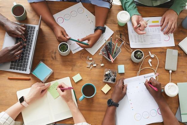 Bovenaanzicht van een multi-etnische groep mensen die samenwerken aan een rommelige houten tafel met koffiekopjes, mokken en stationaire items, teamwerk of studeren concept Premium Foto