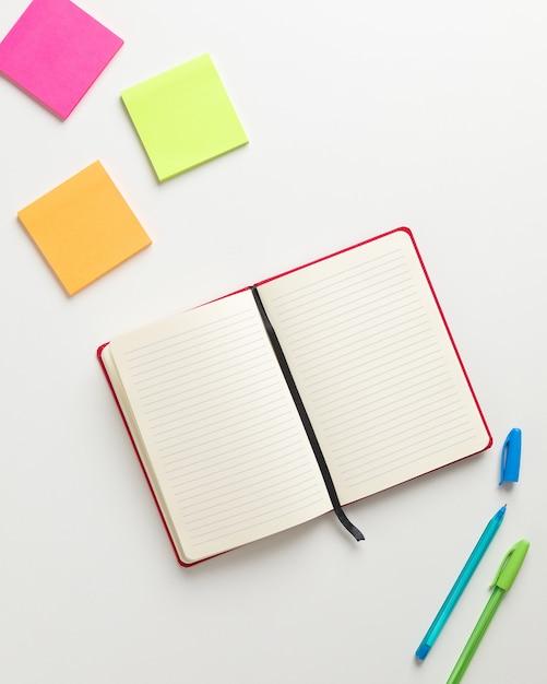 Bovenaanzicht van een open blanco rode notebook in het midden, gekleurde herinneringen in de hoge hoek en blauwe en groene pen in de benedenhoek Premium Foto