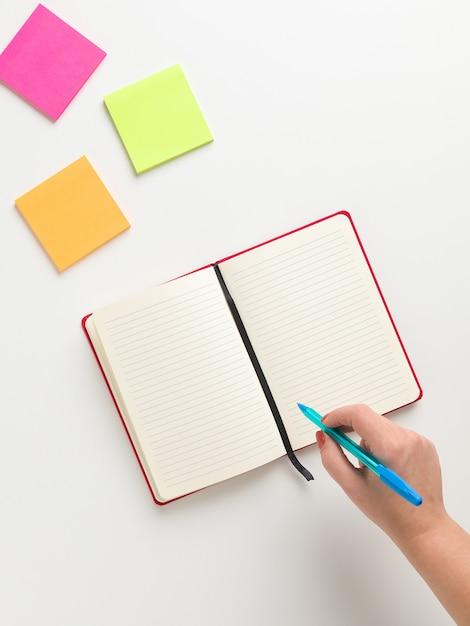 Bovenaanzicht van een open blanco rode notebook in het midden, gekleurde herinneringen in hoge hoek en een vrouwelijke hand met een blauwe pen Premium Foto