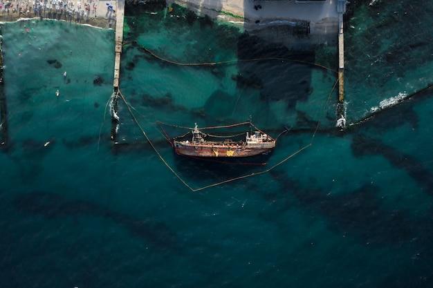 Bovenaanzicht van een oude tanker die aan de grond liep en omviel Gratis Foto
