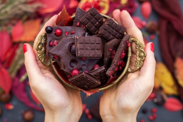 Bovenaanzicht van een persoon met kleine heerlijke veganistische chocoladerepen met bessen Gratis Foto