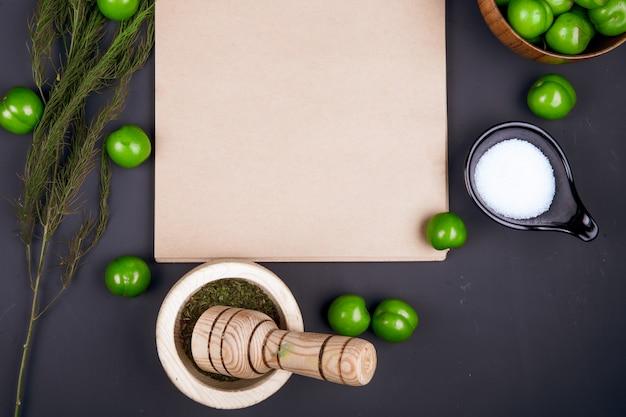Bovenaanzicht van een schetsboek, zout, gedroogde pepermunt in een vijzel, venkel en zure groene pruimen verspreid over zwarte tafel Gratis Foto