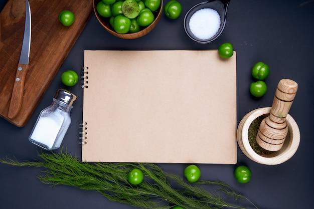 Bovenaanzicht van een schetsboek, zoutvaatje, gedroogde pepermunt in een vijzel en zure groene pruimen in een houten kom op zwarte tafel Gratis Foto