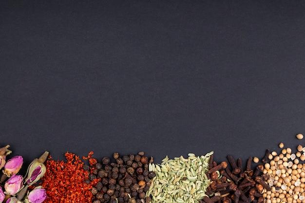 Bovenaanzicht van een set van specerijen en kruiden thee roos toppen rode chili peper vlokken zwarte peper korrels anijs zaden en kruidnagel op zwarte achtergrond met kopie ruimte Gratis Foto