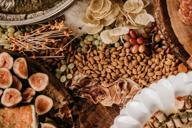 Bovenaanzicht van een tafel vol amandelen, ham, vijgen en droog fruit Gratis Foto