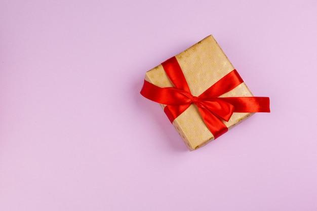 Bovenaanzicht van een versierd heden met een strik op roze achtergrond Premium Foto