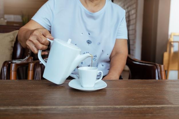 Bovenaanzicht van een vrouwelijke gieten thee op houten tafel Premium Foto