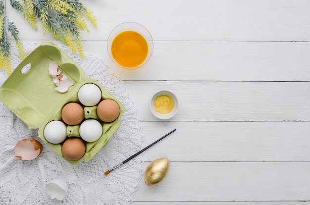 Bovenaanzicht van eieren in karton voor pasen en kleurstof met kwast Gratis Foto