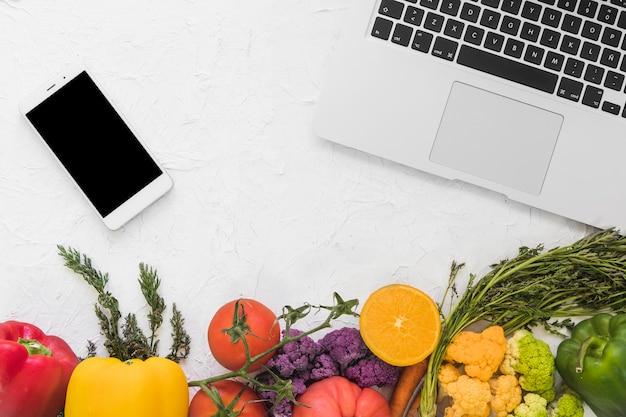 Bovenaanzicht van elektronische apparaten en groenten op witte ondergrond Gratis Foto
