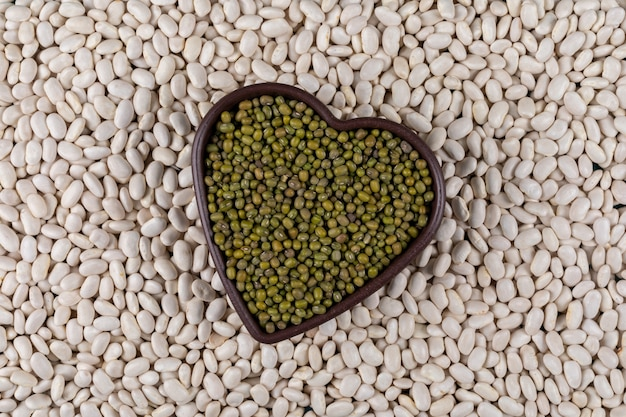 Bovenaanzicht van erwten in hartvormige kom met witte bonen Gratis Foto