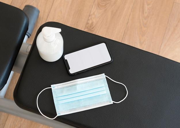 Bovenaanzicht van fitnessapparatuur met medisch masker en handdesinfecterend middel Gratis Foto