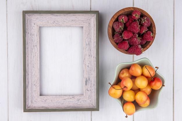 Bovenaanzicht van frambozen met wit frame en witte kers op een wit oppervlak Gratis Foto
