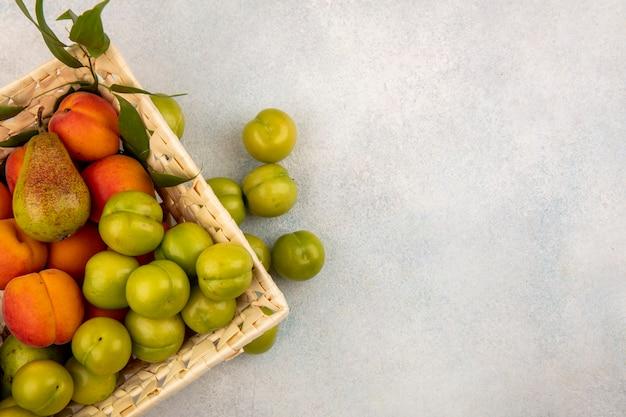 Bovenaanzicht van fruit als peren-abrikozenpruim in mand en op witte achtergrond met exemplaarruimte Gratis Foto