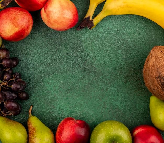 Bovenaanzicht van fruit als perzik kokosnoot appel peer banaan druif op groene achtergrond met kopie ruimte Gratis Foto