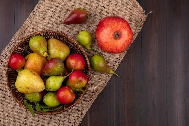 Bovenaanzicht van fruit als pruim van de perzikappel in mand met granaatappel op jute op houten oppervlakte Gratis Foto