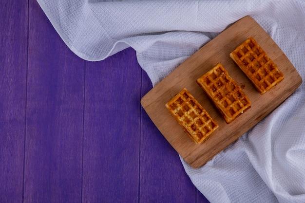 Bovenaanzicht van gebak op witte doek op paarse achtergrond Gratis Foto