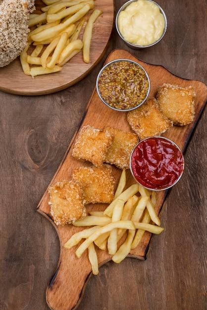 Bovenaanzicht van gebakken kip met frietjes en verschillende soorten saus Gratis Foto