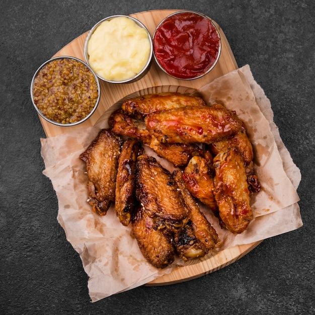 Bovenaanzicht van gebakken kippenvleugels met verschillende sauzen Premium Foto