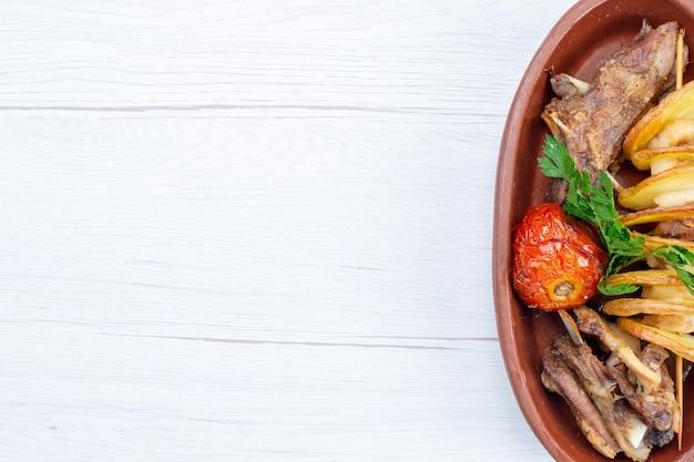 Bovenaanzicht van gebakken vlees met groenen en gebakken pruimen binnen bruine plaat op licht bureau, voedsel maaltijd vleesgerecht diner Gratis Foto