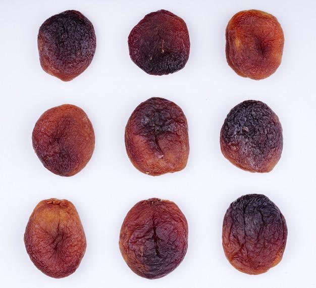 Bovenaanzicht van gedroogde abrikozen geïsoleerd op een witte achtergrond Gratis Foto