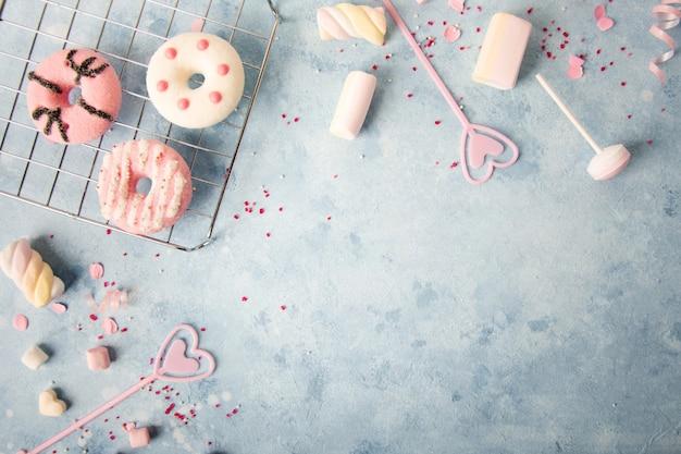 Bovenaanzicht van geglazuurde donuts met assortiment van snoep en marshmallow Gratis Foto