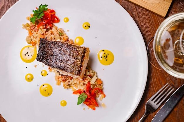 Bovenaanzicht van gegrilde visfilet geserveerd bovenop de couscous salade met paprika Gratis Foto