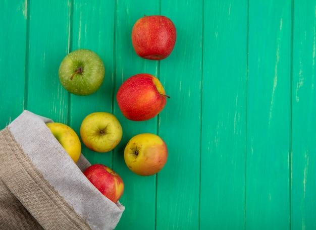 Bovenaanzicht van gekleurde appels in een jutezak op een groen oppervlak Gratis Foto