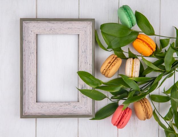 Bovenaanzicht van gekleurde macarons met wit frame en bladtakken op een wit oppervlak Gratis Foto