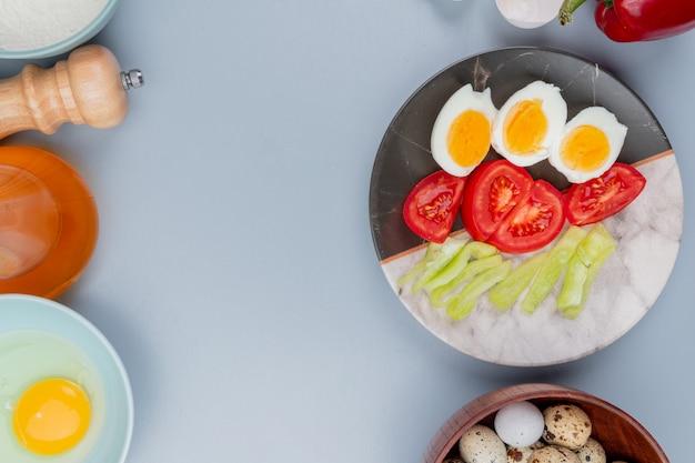 Bovenaanzicht van gekookt ei op een plaat met plakjes tomaten met kwarteleitjes op een houten kom op een witte achtergrond met kopie ruimte Gratis Foto