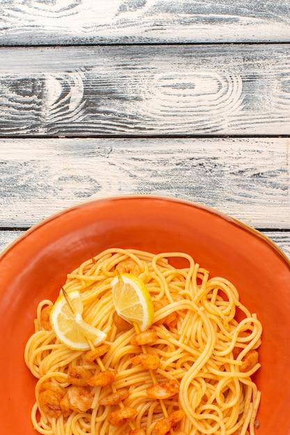 Bovenaanzicht van gekookte italiaanse pasta lekker met plakjes citroen en garnalen in oranje plaat op het grijze houten rustieke oppervlak Gratis Foto