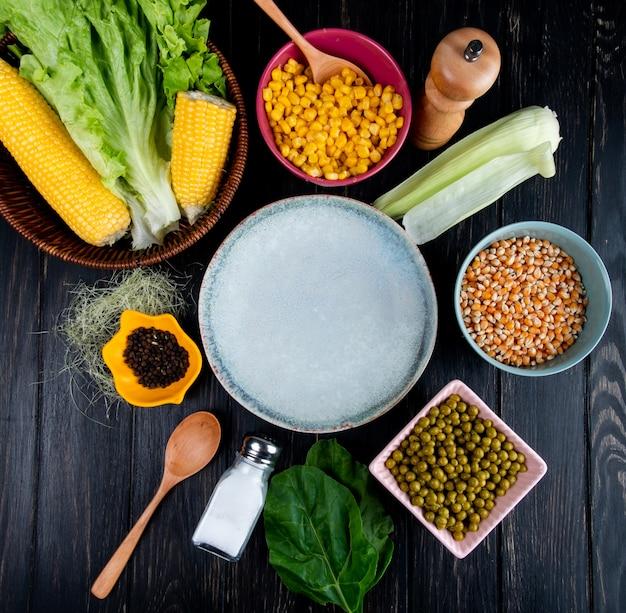 Bovenaanzicht van gekookte likdoorns maïs zaden lege plaat sla met maïs shell en zijde zwarte peper groene erwten zout lepel spinazie op zwart Gratis Foto