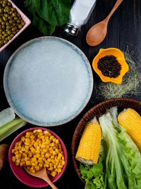 Bovenaanzicht van gekookte likdoorns maïs zaden lege plaat sla met maïs zijde zout lepel spinazie op zwarte ondergrond Gratis Foto