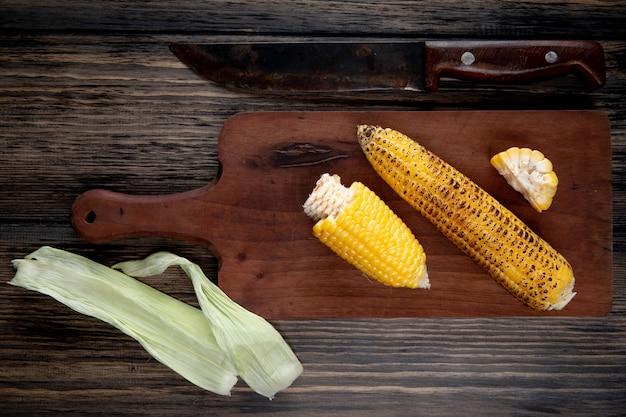 Bovenaanzicht van gekookte likdoorns op snijplank met maïsshell en mes op hout Gratis Foto