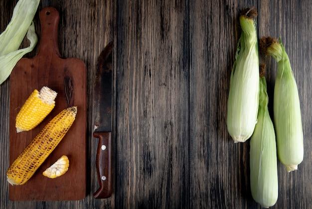Bovenaanzicht van gekookte likdoorns op snijplank met mes en ongekookte likdoorns op hout met kopie ruimte Gratis Foto