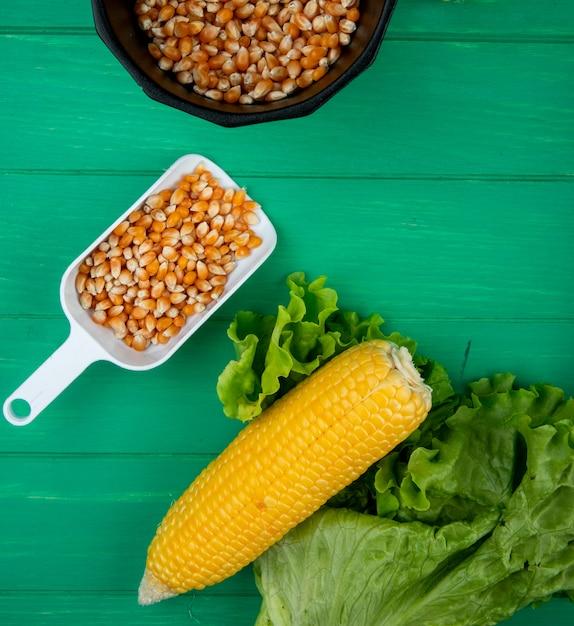 Bovenaanzicht van gekookte maïs met sla en lepel vol maïs zaden op groen Gratis Foto