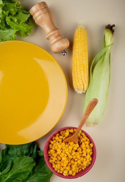 Bovenaanzicht van gekookte maïs zaden met maïskolven spinazie en sla met lege plaat op wit Gratis Foto