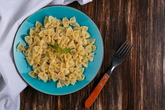 Bovenaanzicht van gekookte pasta op een blauw bord met een vork op een houten oppervlak Gratis Foto