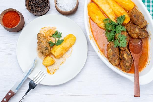 Bovenaanzicht van gekookte vleeskoteletten met pittige sausaardappelen en groene kruiderijen op licht bureau, voedsel maaltijd vlees groente Gratis Foto