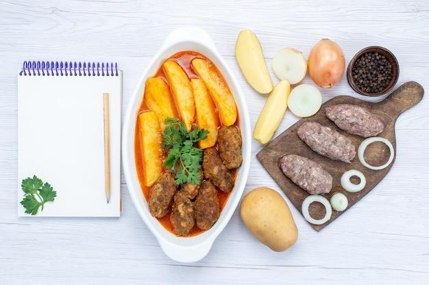 Bovenaanzicht van gekookte vleeskoteletten met sausaardappelen en groen samen met rauw vlees op licht bureau, voedsel maaltijd vlees groente Gratis Foto