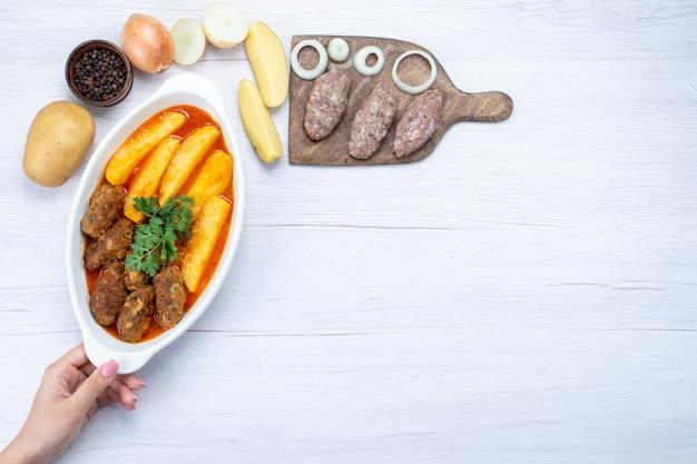 Bovenaanzicht van gekookte vleeskoteletten met sausaardappelen en groen samen met rauw vlees op lichte, voedselmaaltijd vleesgroente Gratis Foto