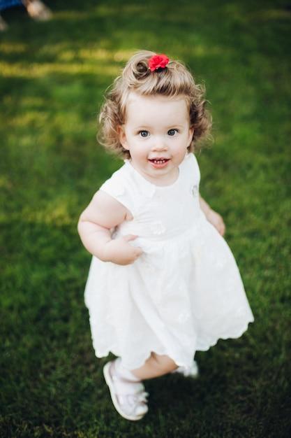 Bovenaanzicht van gelukkig schattig peuter meisje met krullend haar staan in de tuin en kijken naar de camera Gratis Foto