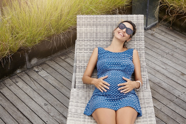 Bovenaanzicht van gelukkige aanstaande moeder in tinten en blauwe jurk rust op een ligstoel, houdt haar dikke buik vast en voelt zich verbonden met haar ongeboren kind. Gratis Foto