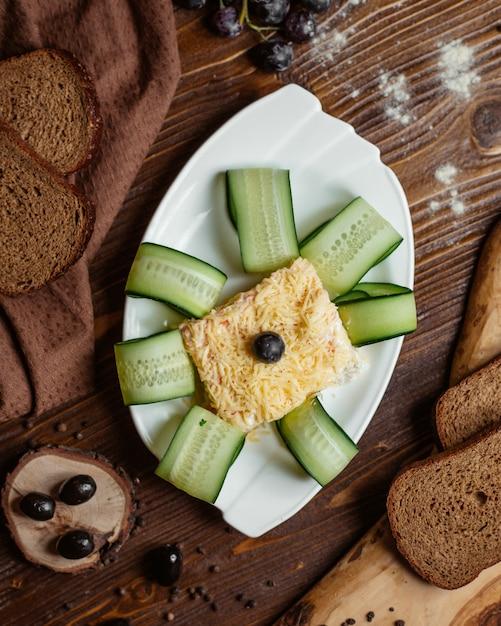 Bovenaanzicht van geportioneerde mimosa salade in witte schotel gegarneerd met plakjes komkommer Gratis Foto