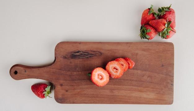 Bovenaanzicht van gesneden aardbeien op een houten snijplank op wit Gratis Foto